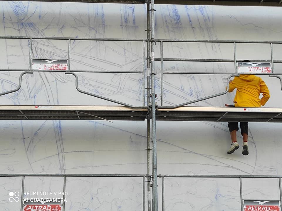 Artiste peintre sur l'échafaudage, en train de peindre la fresque du Festival Paimpol Mon Amour