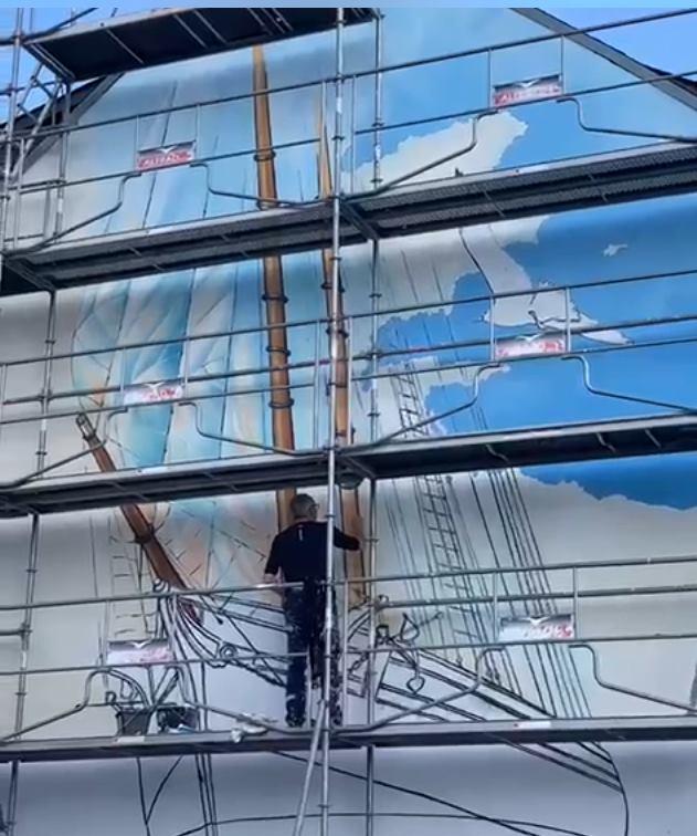 Thibauld de la Corbière sur l'échafaudage en train de peindre les mats du bateau de la fresque.